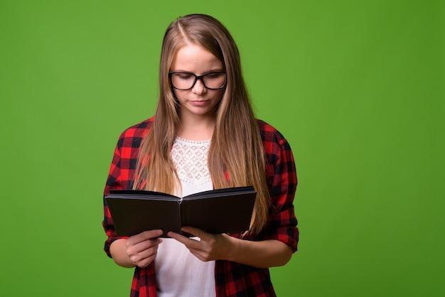 Портрет молодой красивой битник женщины со светлыми волосами на зеленом