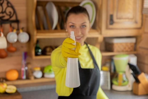 Портрет молодой красивой домохозяйки в черном фартуке, стоящей со спреем для уборки кухни
