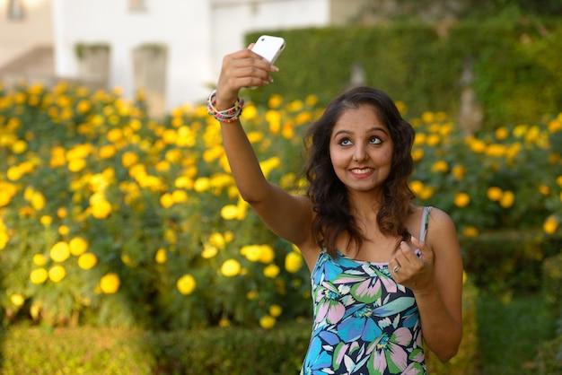 Портрет молодой красивой индийской женщины, расслабляющейся в парке на открытом воздухе