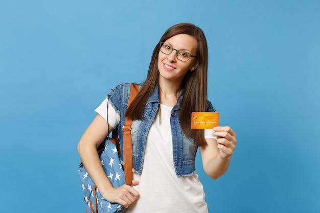 デニムの服を着た若い美しい興味のある楽しい女性学生の肖像画、バックパックのメガネは青い背景で隔離のクレジットカードを保持します。高校大学カレッジコンセプトの教育。