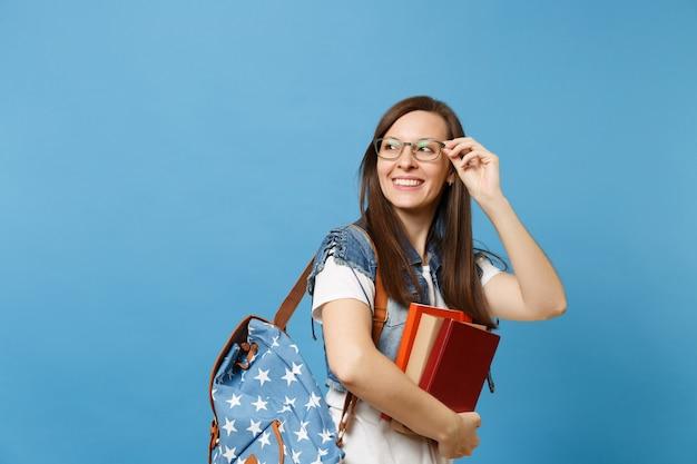 파란색 배경에 격리된 복사 공간을 제쳐두고 배낭 학교 책을 들고 안경을 들고 있는 젊고 즐거운 여성 학생의 초상화. 고등학교 대학 대학 개념의 교육입니다.