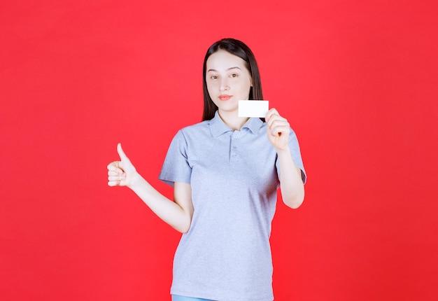 訪問カードを持ち、親指を上にジェスチャーする美しい若い女性のポートレート