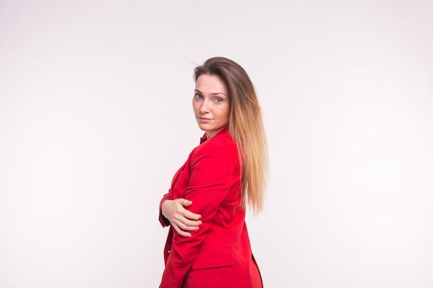 白い壁に赤いジャケットを着た若い美しい女性の肖像画。