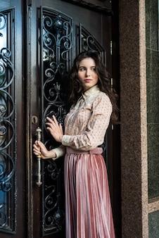 若い美しい女性の肖像画は、古いテクスチャのドアの近くでポーズをとってファッション布を着る