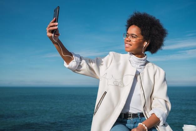 宇宙の海と屋外で彼女の携帯電話でselfiesを取る若い美しいラテン女性の肖像画。