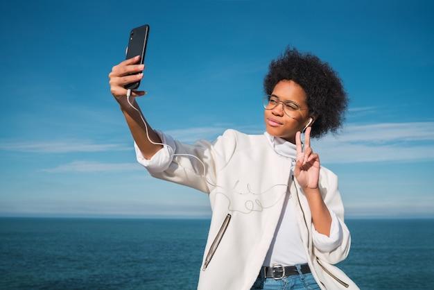 海を上にして屋外で携帯電話で自分撮りをしている若い美しいラテン女性の肖像画。