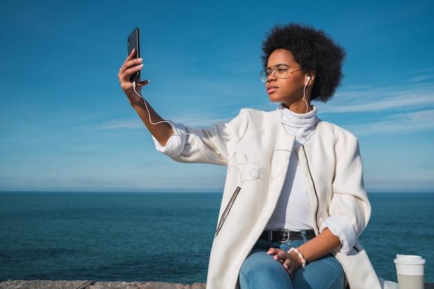 海と屋外で彼女の携帯電話でselfiesを取っている若い美しいラテン女性の肖像画