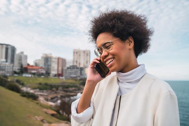 屋外の電話で話している若い美しいラテン女性の肖像画。コミュニケーションの概念。