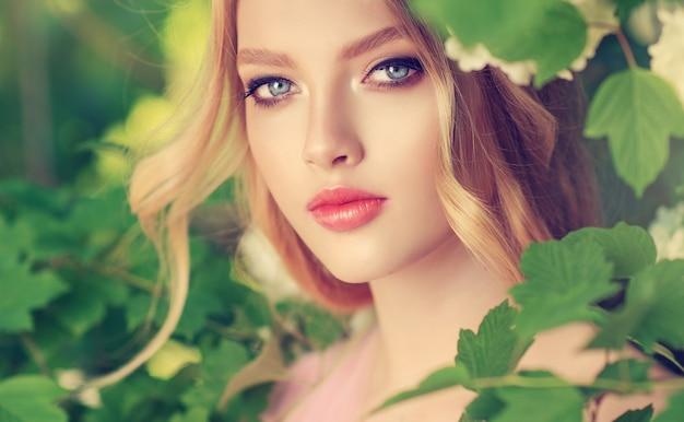 그녀의 긴 곱슬 금발 머리 여성의 아름다움과 청소년 메이크업 및 헤어 스타일의 꽃에 신선한 녹색 정원 나무 빛 바람의 그림자에서 젊은 아름 다운 찾고 모델의 초상화