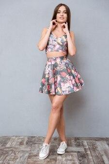 Портрет молодой красивой прекрасной чувственной женщины в летнем цветочном костюме, касающейся ее шеи