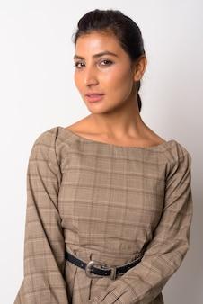 Портрет молодой красивой персидской женщины против белой стены