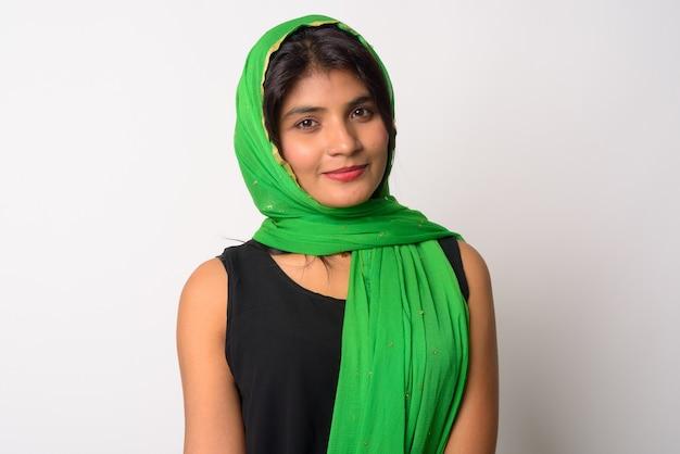 Портрет молодой красивой персидской женщины в традиционной одежде у белой стены