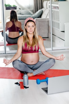 ヨガマットの上に座っている若い美しい妊婦の肖像画