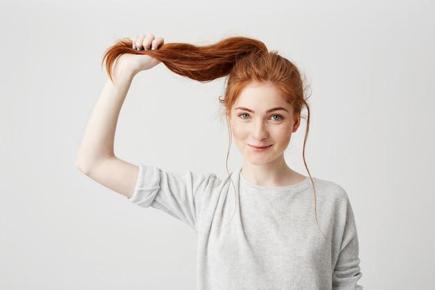彼女の髪の尾に触れる若い美しい赤毛の女の子の肖像画。