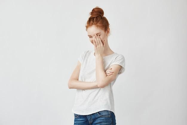 手で顔を笑って若い美しい赤毛の内気な女性の肖像画。白。