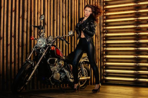 Портрет молодой красивой сексуальной брюнетки модницы в кожаной куртке и кожаных штанах, стоит рядом со своим мотоциклом