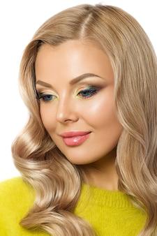 黄色いセーターを着ている若い美しい笑顔金髪女性の肖像画