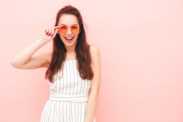 トレンディな夏の流行に敏感なオーバーオールの服を着た若い美しい笑顔の女性の肖像画