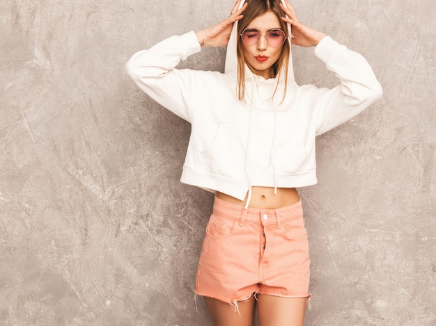 Портрет молодой красивой улыбающейся девушки в модной летней спортивной одежды. сексуальная беззаботная женщина позирует. позитивная модель с удовольствием в солнцезащитных очках
