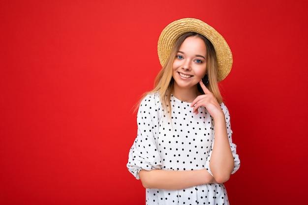 トレンディな夏のドレスとセクシーな麦わら帽子の若い美しい笑顔の流行に敏感なブロンドの女性の肖像画