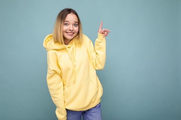Портрет молодой красивой улыбающейся хипстерской блондинки в модной желтой толстовке с сексуальным беззаботным