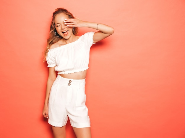 トレンディな夏服の若い美しい笑顔内気な少女の肖像画。セクシーな屈託のない女性がピンクの壁に近いポーズします。楽しいポジティブモデル