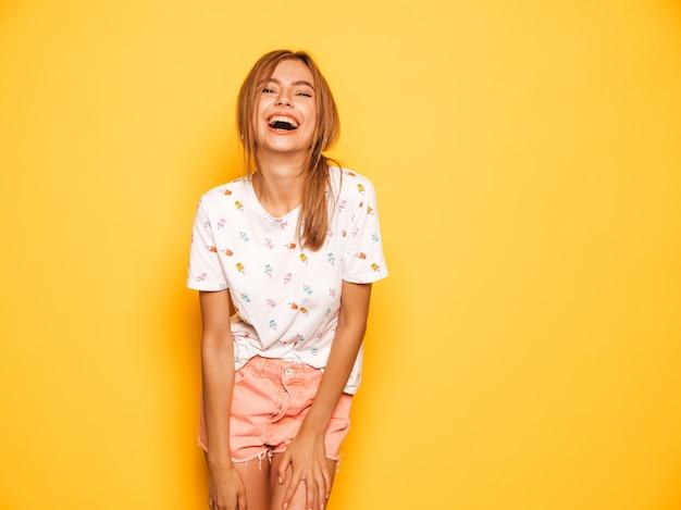 Портрет молодой красивой улыбающейся хипстерской девочки в модных летних джинсах шорты одевается. сексуальная беззаботная женщина позирует возле желтой стены. позитивная модель с удовольствием