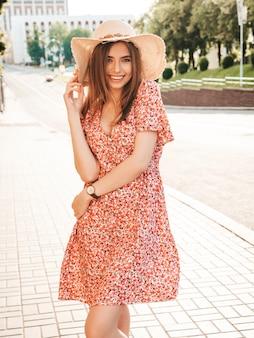 유행 여름 sundress에 젊은 아름 다운 웃는 hipster 여자의 초상화. 일몰에 모자에 거리 배경에 포즈 섹시 평온한 여자. 긍정적 인 모델 야외