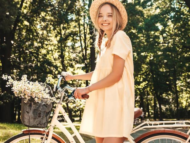 Портрет молодой красивой улыбающейся хипстерской женщины в модном летнем сарафане