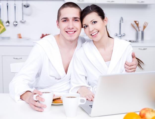 노트북과 부엌에서 젊은 아름 다운 웃는 연인의 초상화
