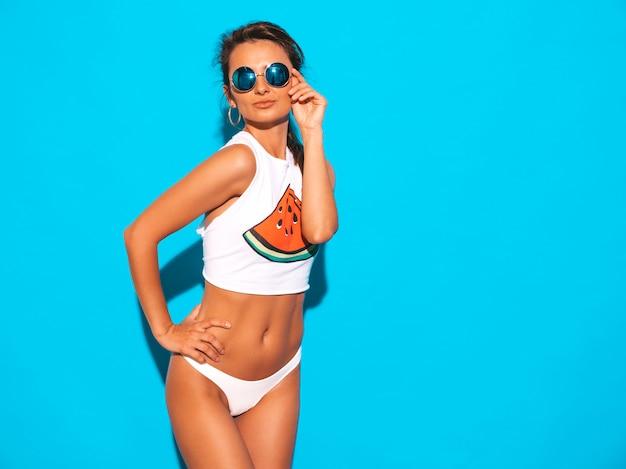 하얀 여름 속옷과 주제에 젊은 아름 다운 웃는 섹시 한 여자의 초상화. 선글라스에 유행 소녀입니다. 긍정적 인 여성 미쳐. 고립 된 재미있는 모델