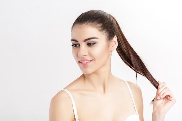 Портрет молодой красивой улыбающейся женщины-брюнетки с естественным макияжем