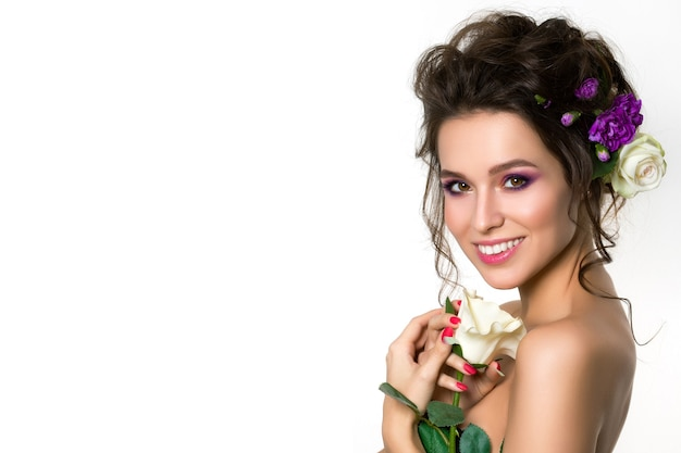 彼女の髪のポーズで紫の花と白いバラを保持している若い美しい笑顔の女性の肖像画。明るい夏のファッションが構成します。ピンクの唇とスモーキーな目。コピースペース
