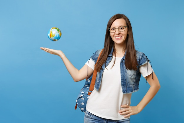 Портрет молодой красивой улыбающейся студентки в джинсовой одежде и очках с рюкзаком, подбрасывающим глобус мира, изолированный на синем фоне. образование в концепции колледжа университета средней школы.
