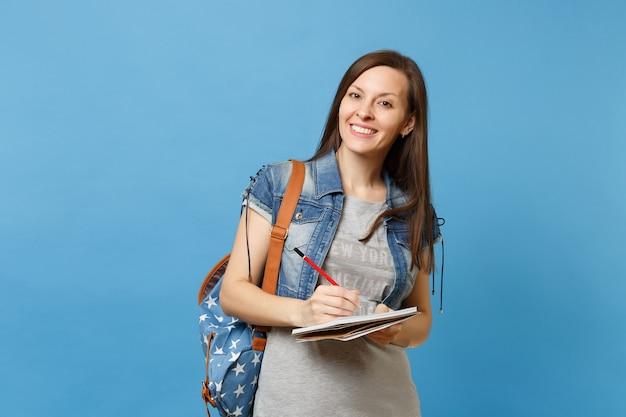 Портрет молодой красивой улыбающейся студентки в серой джинсовой одежде футболки с запиской сочинительства рюкзака на тетради изолированной на голубой предпосылке. образование в концепции колледжа университета средней школы.
