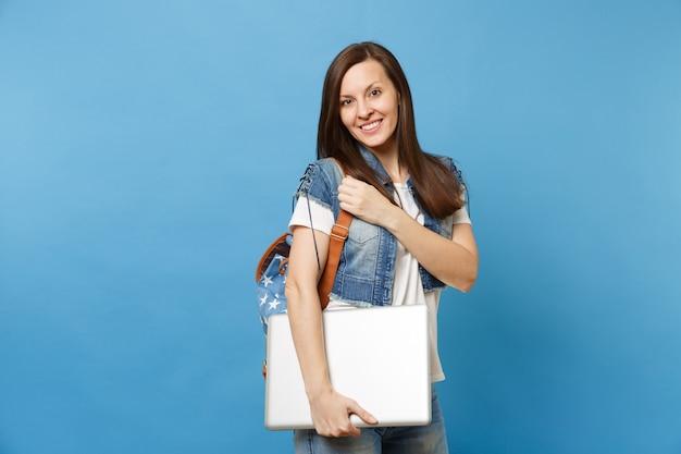 Портрет молодой красивой улыбающейся женщины-студента в футболке, джинсовой одежде с рюкзаком, держащим портативный компьютер, изолированный на синем фоне. обучение в университете. скопируйте место для рекламы.