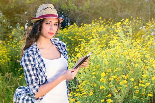 야외에서 타블렛으로 젊은 아름 다운 웃는 여자의 초상화