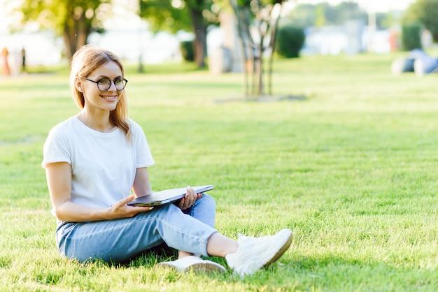 タブレットpc、屋外で若い美しい笑顔の女性の肖像画