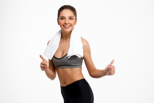 Портрет молодой красивой спортивной девушки на белом фоне.