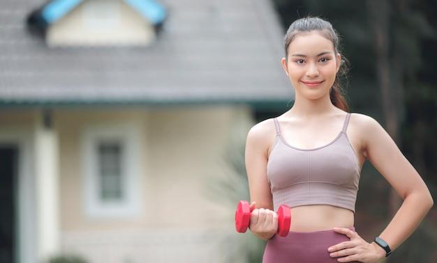 赤いダンベルを押し、笑みを浮かべて、家の前に屋外で立っている間カメラを見て若い美しいスポーツウーマンの肖像画。