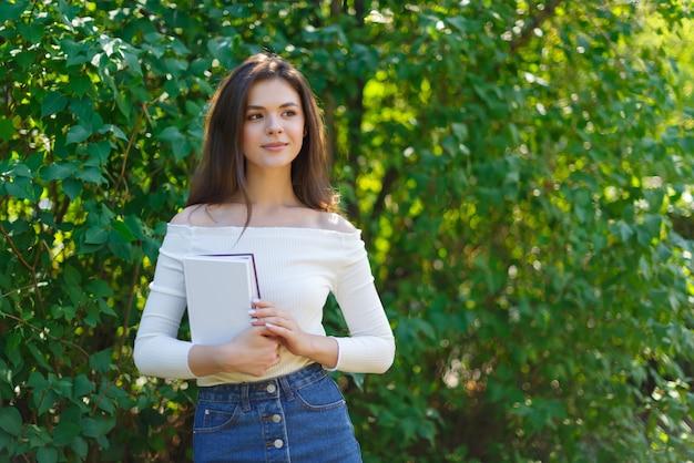 本を持つ若い美しい学生女性の女の子の肖像画