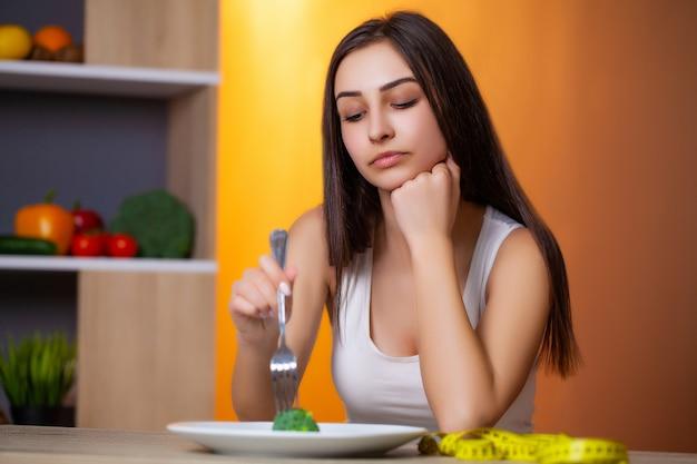ダイエット体制に固執する若い美しい女性の肖像画