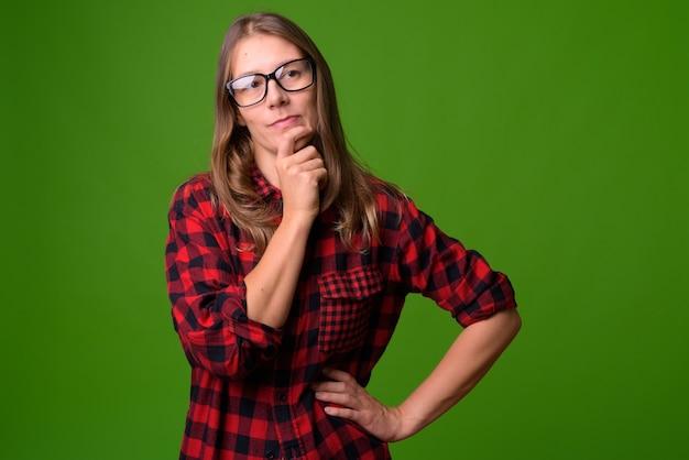 緑の壁に対する若い美しい女性の肖像画