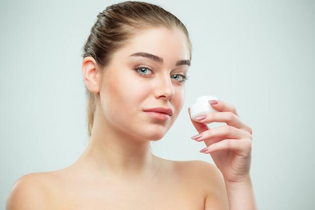 Портрет молодой красивой женщины, применяя увлажняющий крем на лице