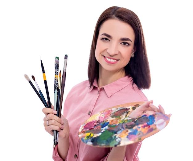 白い背景で隔離のパレットとペイントブラシを持つ若い美しい女性アーティストの肖像画