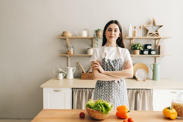 自宅で料理を調理するキッチンに立っている若い美しい女性シェフの肖像画