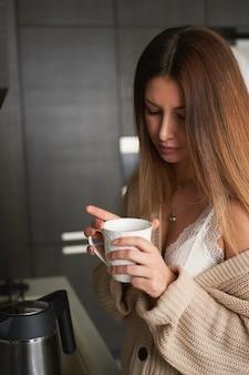 キッチンで自宅でコーヒーを飲む若い美しい女性の肖像画