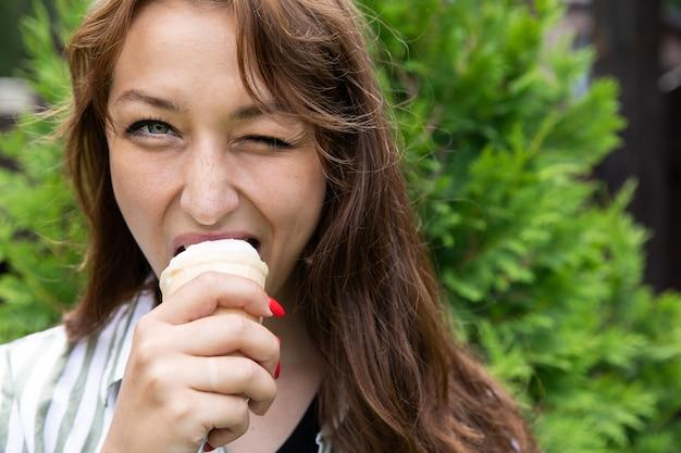 Портрет молодой красивой женщины, едящей мороженое