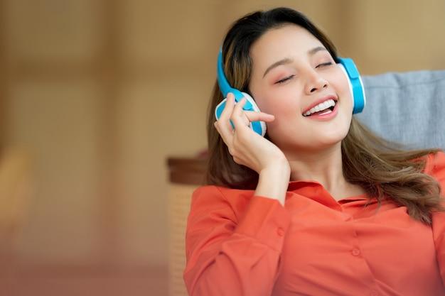 Портрет молодой красивой женщины, наслаждающейся музыкой со смайликом, сидя в творческом офисе или кафе