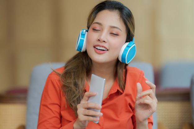 Портрет молодой красивой женщины, наслаждающейся музыкой с улыбающимся лицом, сидя у окна в творческом офисе или кафе